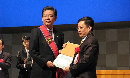 カンボジア政府から友好勲章を受章する北橋健治・北九州市長