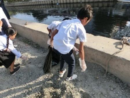 小学校の周囲の水路の清掃活動を行う小学生