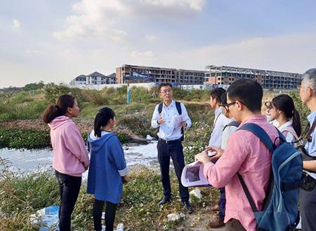 下水処理場予定地で現地大学生に下水道の説明をする専門家